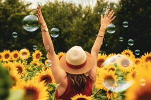 Woman happy in a sunflower field after learning other uses of kratom