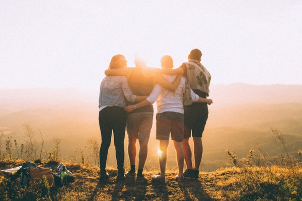A group of people looking at the sunset happy after trying different kratom strains