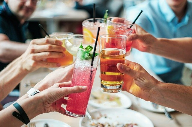People toasting with colorful cocktails.