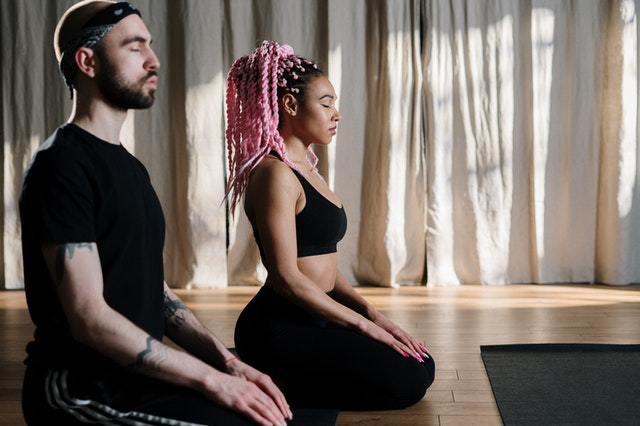 A couple meditating to relieve anxiety
