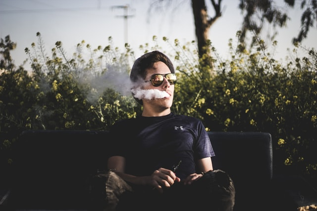 A young man sitting on a bench vaping CBD